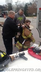 Firefighter Weston helping kid try on the air pack.